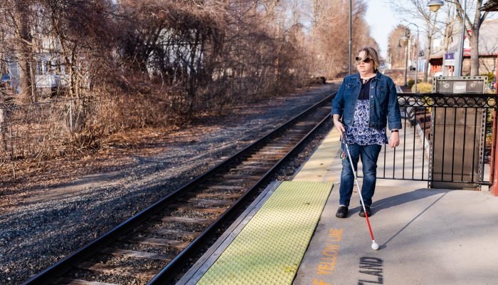 visually impaired woman at train station. demonstrating how her cane helps her get around.